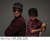 Купить «Hipster father and son in caps and spectacles eyeglasses», фото № 29256225, снято 20 октября 2017 г. (c) Pavel Biryukov / Фотобанк Лори