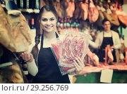 Купить «Female brunette selling jamon in delicatessen store», фото № 29256769, снято 19 октября 2018 г. (c) Яков Филимонов / Фотобанк Лори