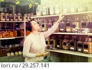 Купить «Female customer selecting various herbs», фото № 29257141, снято 15 ноября 2018 г. (c) Яков Филимонов / Фотобанк Лори