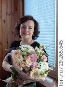Купить «Женщина средних лет с букетом цветов», эксклюзивное фото № 29265645, снято 16 июля 2017 г. (c) Дмитрий Неумоин / Фотобанк Лори