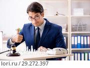 Купить «Young lawyer playing chess to train his court strategy and tacti», фото № 29272397, снято 31 июля 2018 г. (c) Elnur / Фотобанк Лори