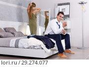 Купить «Man sitting on bed and dressing», фото № 29274077, снято 24 сентября 2018 г. (c) Яков Филимонов / Фотобанк Лори