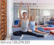 Купить «Man and woman doing stretching exercises», фото № 29274321, снято 18 июля 2018 г. (c) Яков Филимонов / Фотобанк Лори
