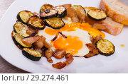 Купить «Cooked scrambled eggs with zucchini and fried lard at plate on table», фото № 29274461, снято 17 ноября 2018 г. (c) Яков Филимонов / Фотобанк Лори