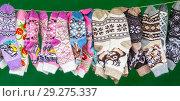 Купить «A lot of colored children's socks on the green background. Showcase street seller», фото № 29275337, снято 16 сентября 2018 г. (c) Михаил Котов / Фотобанк Лори