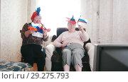 Купить «Two elderly women watching TV in russian accessories and waving Russian flags», видеоролик № 29275793, снято 18 ноября 2018 г. (c) Константин Шишкин / Фотобанк Лори