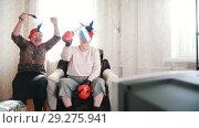 Купить «Two elderly women watching TV in russian accessories and waving Russian flags in slow motion», видеоролик № 29275941, снято 18 ноября 2018 г. (c) Константин Шишкин / Фотобанк Лори