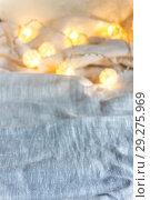 Купить «A garland background with ball lights on the folds of fabric in light gray. Copy space», фото № 29275969, снято 17 января 2018 г. (c) Tetiana Chugunova / Фотобанк Лори
