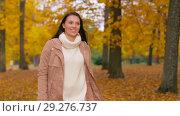 Купить «happy young woman walking in autumn park», видеоролик № 29276737, снято 18 октября 2018 г. (c) Syda Productions / Фотобанк Лори