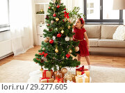 little girl decorating christmas tree at home. Стоковое фото, фотограф Syda Productions / Фотобанк Лори
