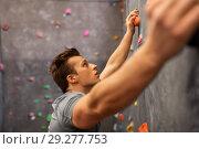Купить «young man exercising at indoor climbing gym», фото № 29277753, снято 2 марта 2017 г. (c) Syda Productions / Фотобанк Лори