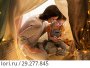 Купить «happy family with smartphone in kids tent at home», фото № 29277845, снято 27 января 2018 г. (c) Syda Productions / Фотобанк Лори