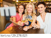 Купить «women taking picture by selfie stick at wine bar», фото № 29278021, снято 25 июня 2018 г. (c) Syda Productions / Фотобанк Лори