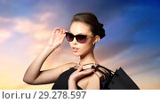 Купить «happy woman in black sunglasses with shopping bags», фото № 29278597, снято 9 апреля 2016 г. (c) Syda Productions / Фотобанк Лори