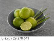 Купить «close up of limes in bowl on slate table top», фото № 29278641, снято 4 апреля 2018 г. (c) Syda Productions / Фотобанк Лори