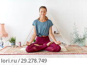 Купить «woman meditating in lotus pose at yoga studio», фото № 29278749, снято 21 июня 2018 г. (c) Syda Productions / Фотобанк Лори