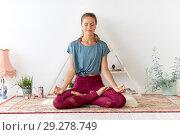 woman meditating in lotus pose at yoga studio. Стоковое фото, фотограф Syda Productions / Фотобанк Лори