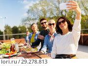 Купить «happy friends taking selfie at rooftop party», фото № 29278813, снято 2 сентября 2018 г. (c) Syda Productions / Фотобанк Лори