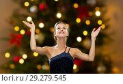 beautiful woman over christmas tree lights. Стоковое фото, фотограф Syda Productions / Фотобанк Лори