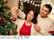 Купить «happy couple decorating christmas tree at home», фото № 29279769, снято 11 января 2018 г. (c) Syda Productions / Фотобанк Лори