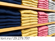 Купить «close up of shelves with clothes at clothing store», фото № 29279797, снято 10 февраля 2018 г. (c) Syda Productions / Фотобанк Лори