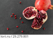Купить «close up of pomegranate on stone table», фото № 29279801, снято 4 апреля 2018 г. (c) Syda Productions / Фотобанк Лори