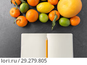Купить «close up of fruits and notebook on slate table top», фото № 29279805, снято 4 апреля 2018 г. (c) Syda Productions / Фотобанк Лори