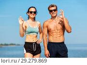 Купить «couple of athletes in shades on beach showing ok», фото № 29279869, снято 1 августа 2018 г. (c) Syda Productions / Фотобанк Лори