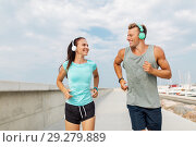 Купить «couple with headphones running outdoors», фото № 29279889, снято 1 августа 2018 г. (c) Syda Productions / Фотобанк Лори