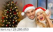 Купить «couple in santa hats over christmas tree lights», фото № 29280053, снято 7 октября 2012 г. (c) Syda Productions / Фотобанк Лори