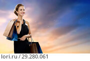 Купить «happy woman in black dress with shopping bags», фото № 29280061, снято 1 июня 2014 г. (c) Syda Productions / Фотобанк Лори