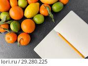 Купить «close up of fruits and notebook on slate table top», фото № 29280225, снято 4 апреля 2018 г. (c) Syda Productions / Фотобанк Лори
