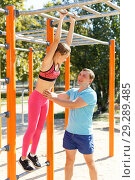 Купить «Man with daughter exercising on chinning bar», фото № 29289485, снято 29 сентября 2018 г. (c) Яков Филимонов / Фотобанк Лори