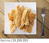 Купить «Top view of deep-fried chicken strips in sesame», фото № 29289953, снято 18 декабря 2018 г. (c) Яков Филимонов / Фотобанк Лори