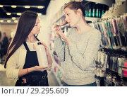 Купить «Young woman hairdresser helping woman client with choice of shampoo in shop», фото № 29295609, снято 31 марта 2018 г. (c) Яков Филимонов / Фотобанк Лори
