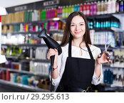 Купить «Woman hairstylist holding blow dryer and hair cutters in cosmetics salon», фото № 29295613, снято 31 марта 2018 г. (c) Яков Филимонов / Фотобанк Лори