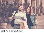 Купить «Couple of tourists with map and baggage hugging», фото № 29295681, снято 25 мая 2017 г. (c) Яков Филимонов / Фотобанк Лори