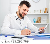 Купить «Smiling young man signing profitable financial agreement», фото № 29295769, снято 5 марта 2017 г. (c) Яков Филимонов / Фотобанк Лори
