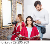 Купить «Positive young man hairdresser cuts hair of young woman with magazine at salon», фото № 29295969, снято 25 апреля 2018 г. (c) Яков Филимонов / Фотобанк Лори