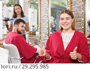 Купить «Smiling young woman client in salon's peignoir holding thumbs up», фото № 29295985, снято 25 апреля 2018 г. (c) Яков Филимонов / Фотобанк Лори