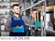 Купить «Master selects necessary materials and tools for repair», фото № 29296045, снято 15 марта 2017 г. (c) Яков Филимонов / Фотобанк Лори