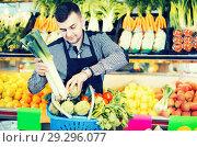Купить «Male shopping assistant helping to buy fruit and vegetables in grocery shop», фото № 29296077, снято 18 марта 2017 г. (c) Яков Филимонов / Фотобанк Лори