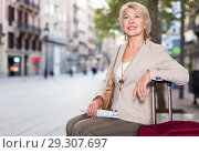 Купить «Adult woman 50-60 years old is sitting with map and suitcase», фото № 29307697, снято 3 сентября 2017 г. (c) Яков Филимонов / Фотобанк Лори