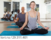 Купить «Young girl meditating in yoga position lotus during group training», фото № 29311401, снято 30 июля 2018 г. (c) Яков Филимонов / Фотобанк Лори