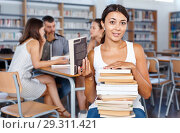 Купить «Smiling female student sitting with pile of books in high school library on background with working coursemates», фото № 29311421, снято 26 июля 2018 г. (c) Яков Филимонов / Фотобанк Лори
