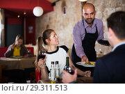Купить «Waiter bringing salads to guests», фото № 29311513, снято 18 декабря 2017 г. (c) Яков Филимонов / Фотобанк Лори