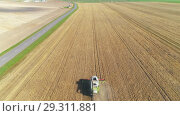 Купить «Aerial view of combine harvester on wheat field. Smooth decrease from height.», видеоролик № 29311881, снято 14 сентября 2018 г. (c) Андрей Радченко / Фотобанк Лори