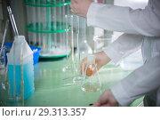 Купить «Chemical laboratory. Young woman holding a flask, pouring something using pipette», фото № 29313357, снято 26 октября 2018 г. (c) Константин Шишкин / Фотобанк Лори