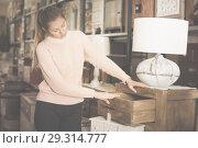 Купить «Woman buyer near chest of drawers», фото № 29314777, снято 15 ноября 2017 г. (c) Яков Филимонов / Фотобанк Лори