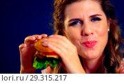 Купить «Woman bite burger and winks. Happy student eat sandwich lunch.», фото № 29315217, снято 20 марта 2019 г. (c) Gennadiy Poznyakov / Фотобанк Лори